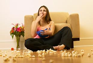 woman eating popcorn on the floor