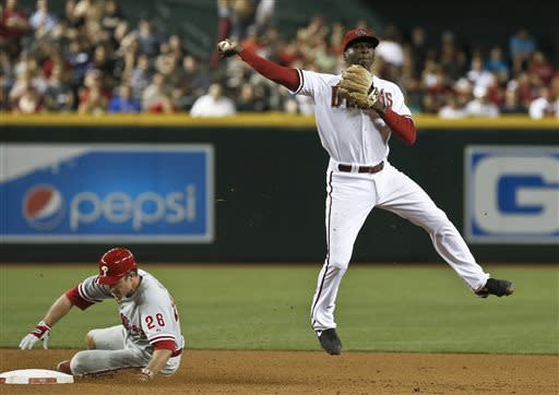 Arizona Diamondbacks' Didi Gregorius, right, throws to first base after forcing out Philadelphia Phillies' Chase Utley (26) during the fifth inning of a baseball game on Friday, May 10, 2013, in Phoenix. (AP Photo/Ross D. Franklin)