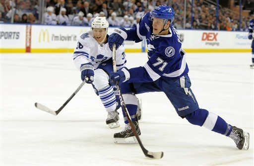 Tampa Bay Lightning right wing Richard Panik, of Slovakia, right, takes a shot in front of Toronto Maple Leafs defenseman Carl Gunnarsson, of Sweden, during the second period of an NHL hockey game Tuesday, Feb. 19, 2013, in Tampa, Fla. (AP Photo/Brian Blanco)