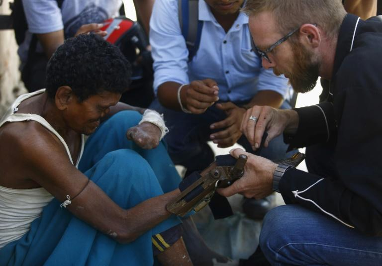Disaster Hack founder Matthew Rockwell (R) attaches a 3D printed prosthetic hand to leprosy sufferer Ram's arm in Kathmandu