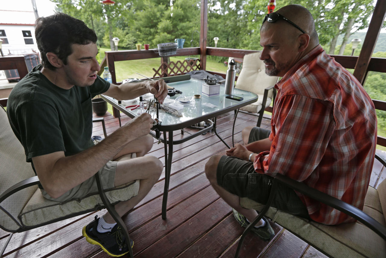In this June 25, 2013 photo, Richard Norris, left, ties a fishing fly at his home in Hillsville, Va., as friend Andrew Kahle looks on. Norris, whose face was disfigured by a gunshot, spent 15 years as a recluse, but now the 37-year-old is doing things he never would have before. (AP Photo/Chuck Burton)