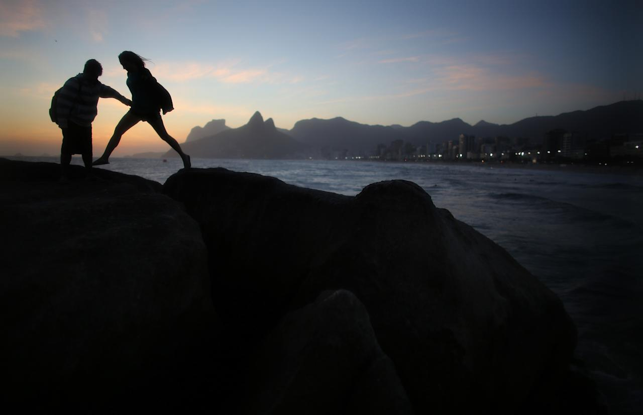 RIO DE JANEIRO, BRAZIL - NOVEMBER 02: A woman jumps across the rocks at Arpoador at sunset on the Day of the Dead on November 2, 2013 in Rio de Janeiro, Brazil. Brazilians often mark the traditional Latin American holiday by visiting loved ones' graves while the Zombie Walk on nearby Copacabana Beach offered a modern twist. (Photo by Mario Tama/Getty Images)