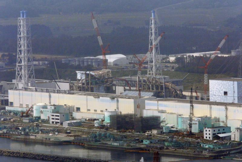 In this aerial photo taken from the Asahi Shimbun helicopter, cranes surround the tsunami-damaged Fukushima Dai-ichi nuclear power plant reactors, from right, Unit 2, covered by light blue walls, Unit 3, center, and Unit 4, in Okuma, Fukushima Prefecture, northeastern Japan, Monday, May 28, 2012. The prime minister during Japan's nuclear crisis last year said Monday he had to use an emergency law that never anticipated major radiation leaks and lacked experts capable of giving him guidance. (AP Photo/Tom Curley)