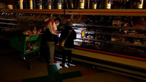 PHOTO: Customers use the light from a cell phone to look in the meat section of a grocery store Tuesday, Feb. 16, 2021, in Dallas. (Lm Otero/AP)
