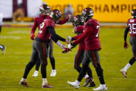 Tampa Bay Buccaneers quarterback Tom Brady (12), left, celebrates with teammates at the end of an NFL wild-card playoff football game against the Washington Football Team, Saturday, Jan. 9, 2021, in Landover, Md. Tampa Bay won 31-23. (AP Photo/Andrew Harnik)