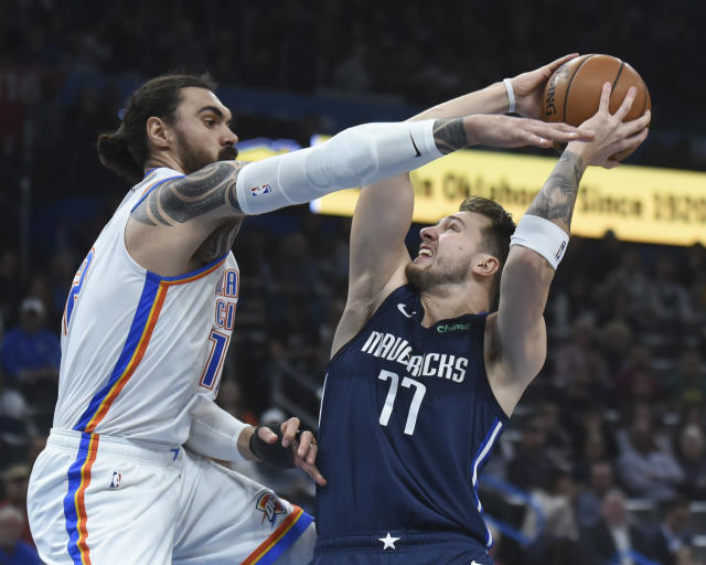 Oklahoma City Thunder center Steven Adams (12) tries to get the ball from Dallas Mavericks guard Luka Doncic (77) in the first half of an NBA basketball game, Monday, Jan. 27, 2020, in Oklahoma City. (AP Photo/Kyle Phillips)