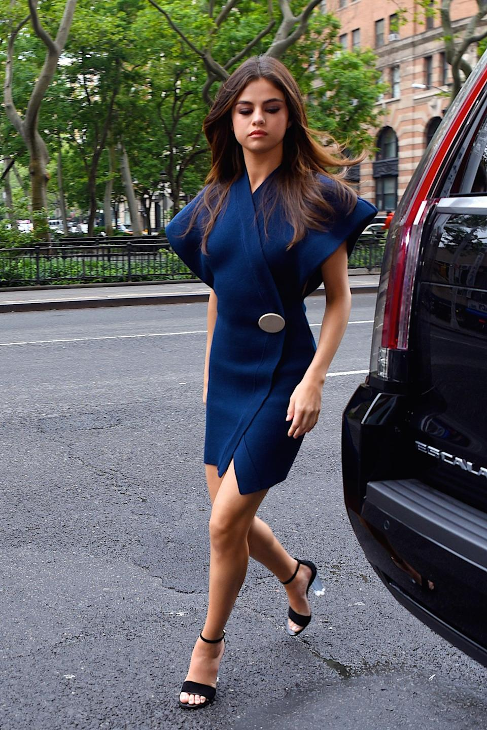 """<p>Because every gal needs a pair of chunky Lucite heels in her closet, we'd encourage you to take a tip from Selena. She stepped out in NYC in June 2017 wearing a <a href=""""https://www.popsugar.com/fashion/Selena-Gomez-Navy-Wrap-Dress-43605175"""" class=""""link rapid-noclick-resp"""" rel=""""nofollow noopener"""" target=""""_blank"""" data-ylk=""""slk:navy Jacquemus wrap dress"""">navy Jacquemus wrap dress</a> and Louis Vuitton shoes, effortlessly mixing blue and black.</p>"""