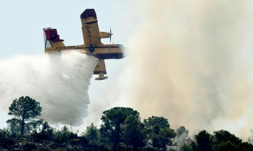 A seaplane drops water over a wildfire tearing through the Spanish town of Pinet, on August 7, 2018