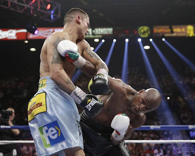 Marcos Maidana, left, from Argentina, trades punches with Floyd Mayweather Jr. in their WBC-WBA welterweight title boxing fight Saturday, May 3, 2014, in Las Vegas. (AP Photo/Isaac Brekken)