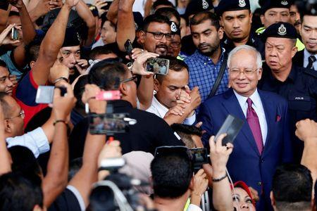 FILE PHOTO:  Malaysia's former Prime Minister Najib greets his supporters as he leaves a court in Kuala Lumpur