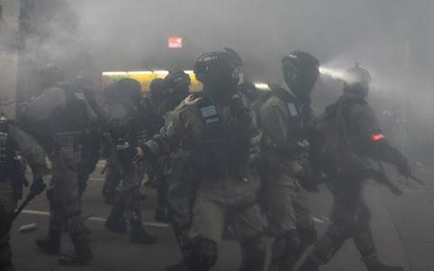 <span>Riot police fire tear gas in central Hong Kong on New Year's Day</span> <span>Credit: Kyle Lam/Bloomberg </span>