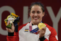 Maude G. Charron of Canada celebrates her gold medal on the podium of the women's 64kg weightlifting event, at the 2020 Summer Olympics, Tuesday, July 27, 2021, in Tokyo, Japan. (AP Photo/Luca Bruno)