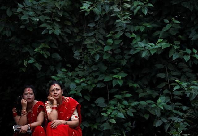 <p>Women look towards people singing and dancing during the Teej festival in Kathmandu, Nepal September 12, 2018. REUTERS/Navesh Chitrakar </p>