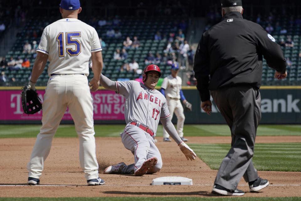 Los Angeles Angels' Shohei Ohtani (17) slides safely into third as Seattle Mariners third baseman Kyle Seager (15) looks on during the third inning of a baseball game, Sunday, May 2, 2021, in Seattle. Ohtani was advancing on a flyout by Angels' Anthony Rendon. (AP Photo/Ted S. Warren)