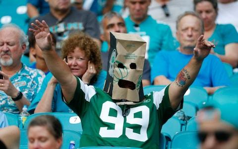 A New York Jets fan wears a paper bag after the team lost to the Miami Dolphins in an NFL football game, Sunday, Nov. 3, 2019, in Miami Gardens - Credit: AP