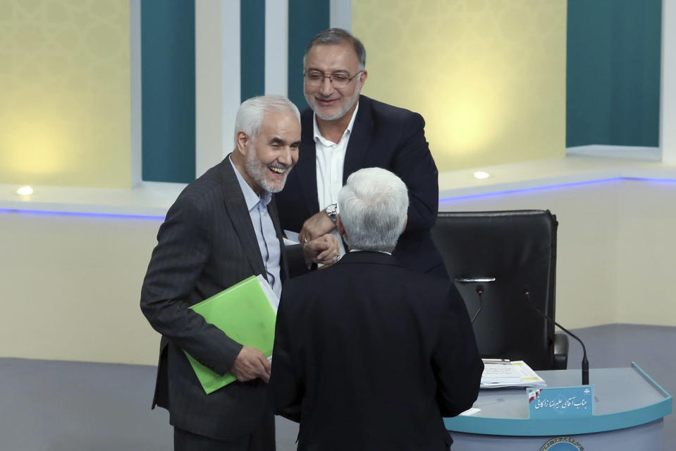 """In this picture made available by Young Journalists Club, YJC, presidential candidates for June 18, elections Mohsen Mehralizadeh, left, Alireza Zakani, top, and Saeed Jalili, talk at the conclusion of a part of the final debate of the candidates at a state-run TV studio in Tehran, Iran, Saturday, June 12, 2021. Iran's seven presidential candidates offered starkly different views Saturday in the country's final debate, with hard-liners describing those seeking ties with the West as """"infiltrators"""" and the race's sole moderate warning a hard-line government would only bring more sanctions for the Islamic Republic. (Morteza Fakhri Nezhad/ Young Journalists Club, YJC via AP)"""