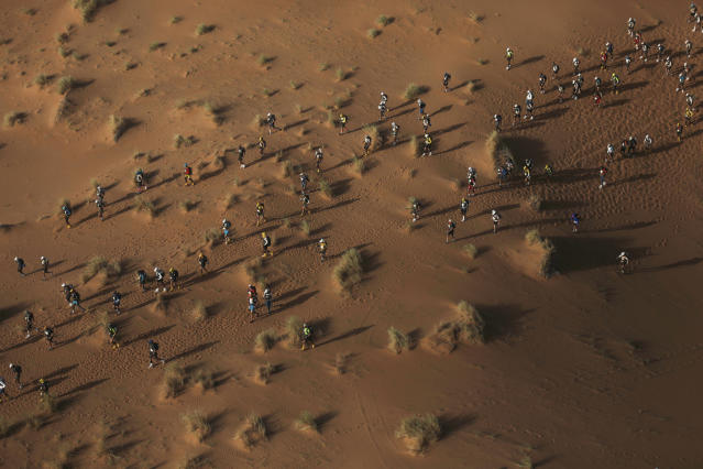An aerial photo shows competitors crossing sand dunes as they take part in in the 33rd edition of Marathon des Sables, in the Sahara desert, near Merzouga, southern Morocco, Friday, April 13, 2018. (AP Photo/Mosa'ab Elshamy)