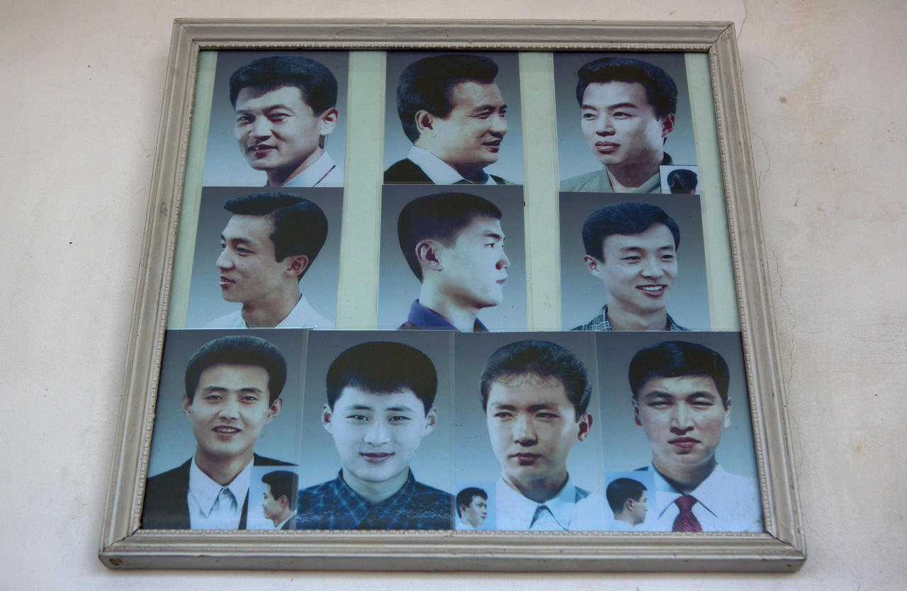 Photos showing example hair styles hang inside a barber shop in Pyongyang, North Korea on Wednesday, Feb. 20, 2013. (AP Photo/David Guttenfelder)
