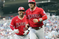 Los Angeles Angels' Kurt Suzuki, left, and Jose Iglesia head to the dugout following a two-run home run by Suzuki off Minnesota Twins pitcher J.A. Happ during the first inning of a baseball game Friday, July 23, 2021, in Minneapolis. (AP Photo/Jim Mone)