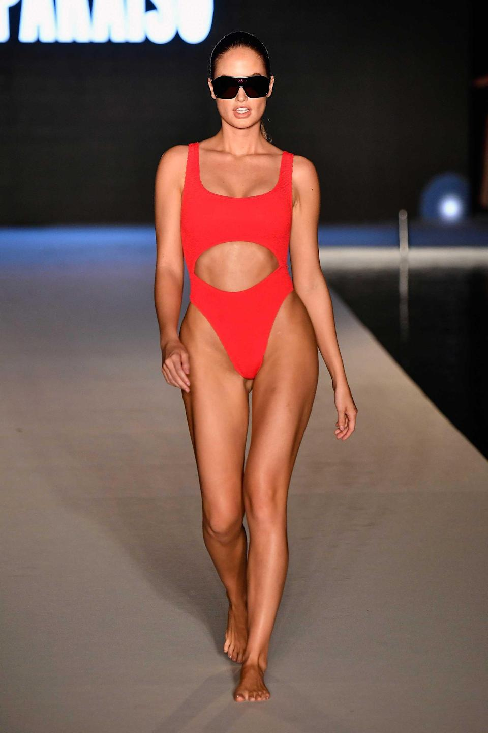 <p>A model walks the runway wearing a red cutout swimsuit for the 2018 <em>Sports Illustrated</em> swimsuit show during the Paraiso Fashion Fair in Miami at the W South Beach hotel on July 15. (Photo: Alexander Tamargo/Getty Images for Sports Illustrated) </p>