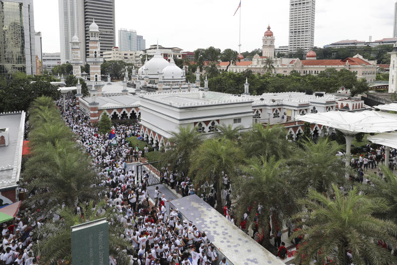 Protesters gather for a rally near a mosque to celebrate the government's move to withdraw plans to ratify a U.N. anti-discrimination convention, in Kuala Lumpur, Malaysia, Saturday, Dec. 8, 2018. Thousands of Malaysian Muslims are rallying in Kuala Lumpur against any attempt to strip ethnic Malay majority of their privileges, in the first massive street gathering since Prime Minister Mahathir Mohamad's alliance won a historic vote in May.(AP Photo/Vincent Thian)