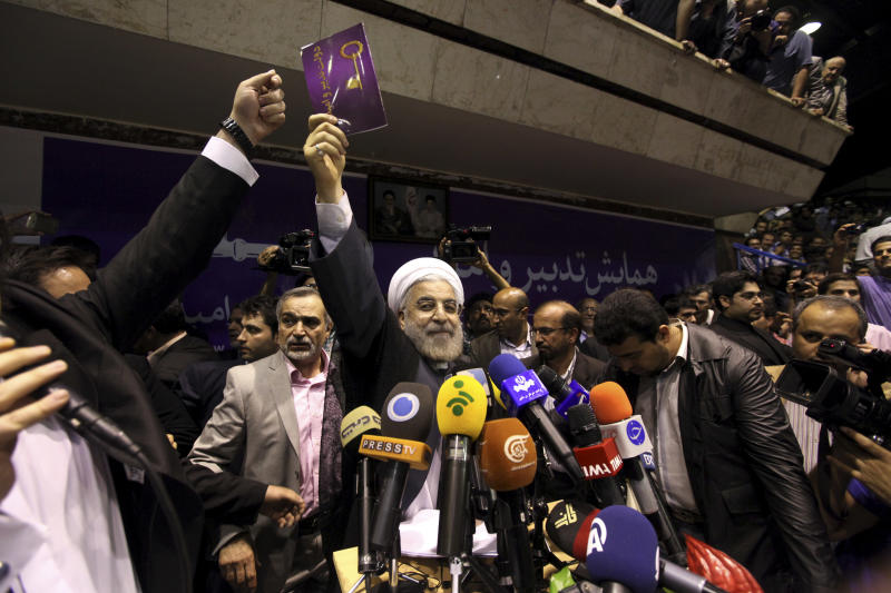 Iranian presidential candidate Hasan Rowhani, center, holds up a leaflet showing a key, the symbol of his campaign, during a rally in Tehran, Iran, Saturday, June 8, 2013. Rowhani, a candidate in next week's presidential elections, says he will reset Iran's economy and will reverse President Mahmoud Ahmadinejad's foreign policy directions if elected. (AP Photo/Ebrahim Noroozi)