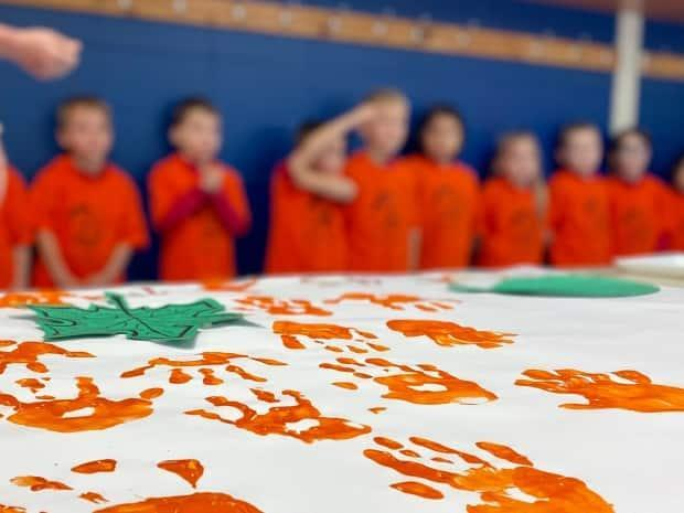 Children at a school in Wendake marked the first National Day for Truth and Reconciliation. They wore orange T-shirts and made a banner with their handprints. (Hadi Hassin/Radio-Canada - image credit)