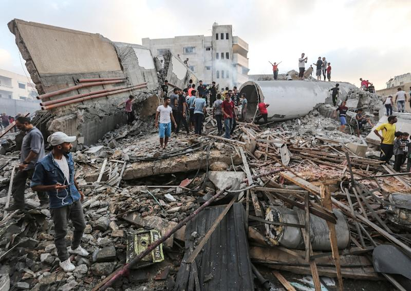 People inspect the rubble of a building after an Israeli air strike on Gaza City, which Palestinians say housed a cultural centre while the Israeli army says it was used by the Islamist Hamas group (AFP Photo/MAHMUD HAMS)