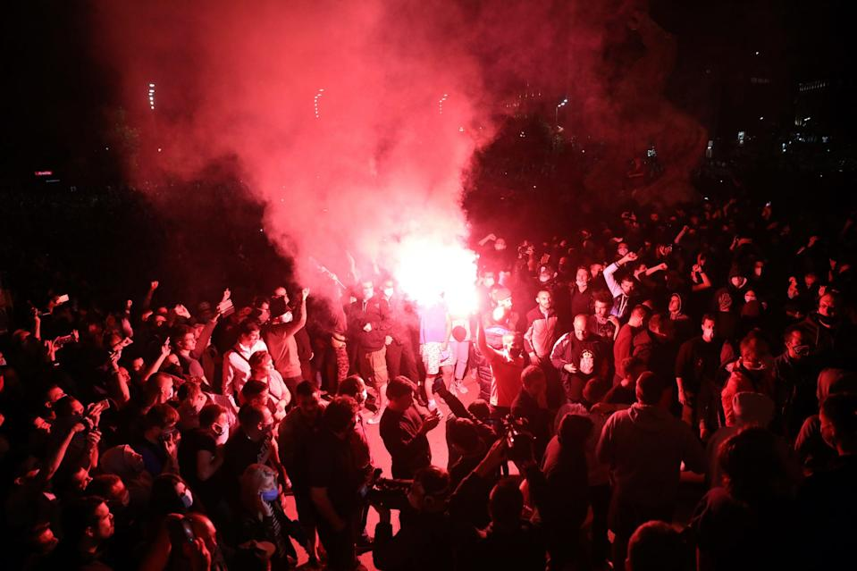 Demonstrators light a flare as they gather during a protest at the Serbian parliament building against a lockdown planned for the capital this weekend to halt the spread of the coronavirus in Belgrade, Serbia, on July 7, 2020.