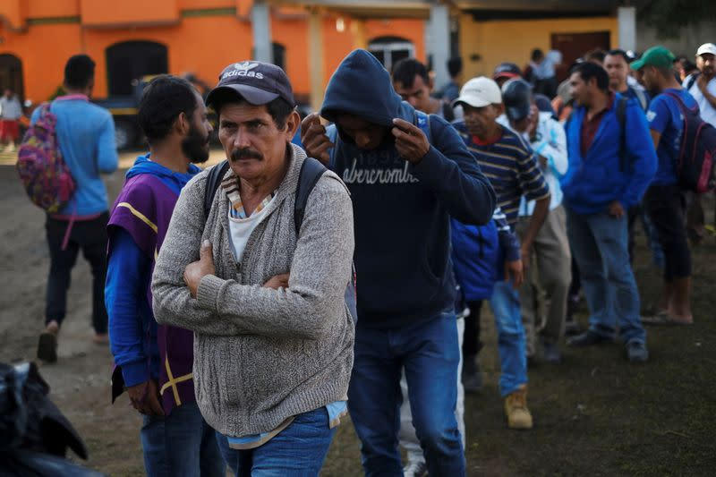 Migrants travelling to the U.S. make a line to get breakfast in an improvised shelter in Tecun Uman