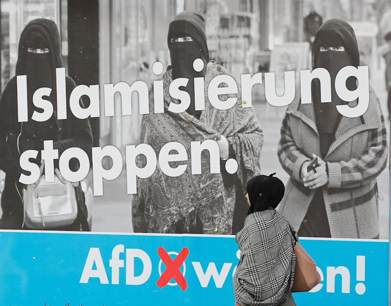 A woman with a headscarf walks past an AfD campaign poster in Marxloh, a suburb of Duisburg, Germany, in which many people have Turkish roots.