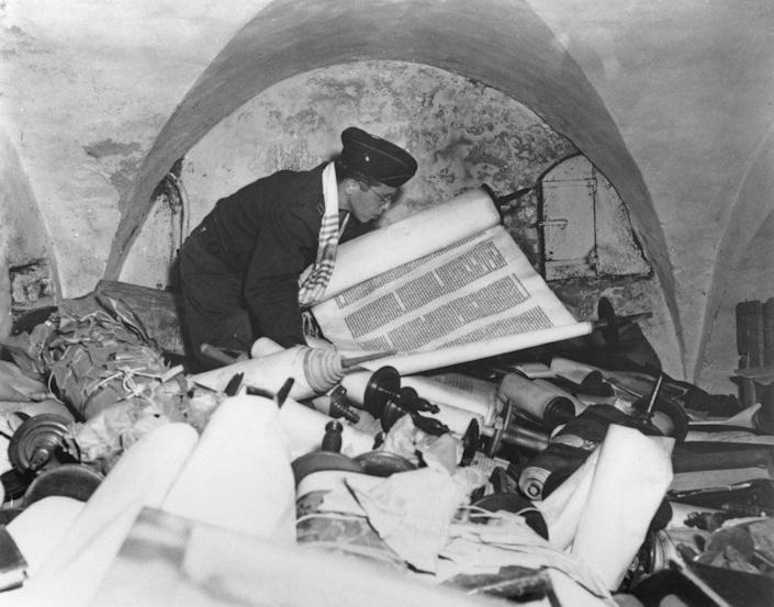 US Army chaplain Samuel Blinder examines one of hundreds of Jewish Sefer Torah scrolls, stolen from all over Europe by Nazi forces, and stored in the cellar of the Kaiser Wilhelm Institute of Anthropology, Human Heredity, and Eugenics (KWI-A) in Frankfurt, Germany, 6th July 1945 (Getty Images)