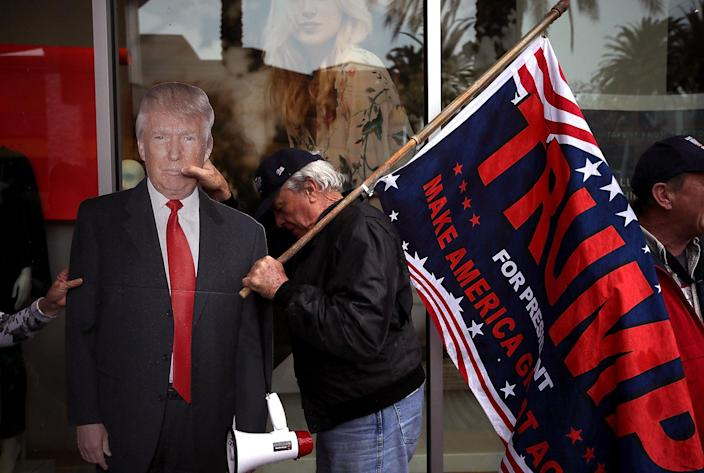 """<p>A supporter of President Donald Trump moves a cardboard cutout of the president away from the rain during a rally outside the office of U.S. Rep. Ed Royce, R-Calif., in favor of the """"America First"""" agenda in Brea, Calif., Feb. 27, 2017. (Photo: Justin Sullivan/Getty Images) </p>"""