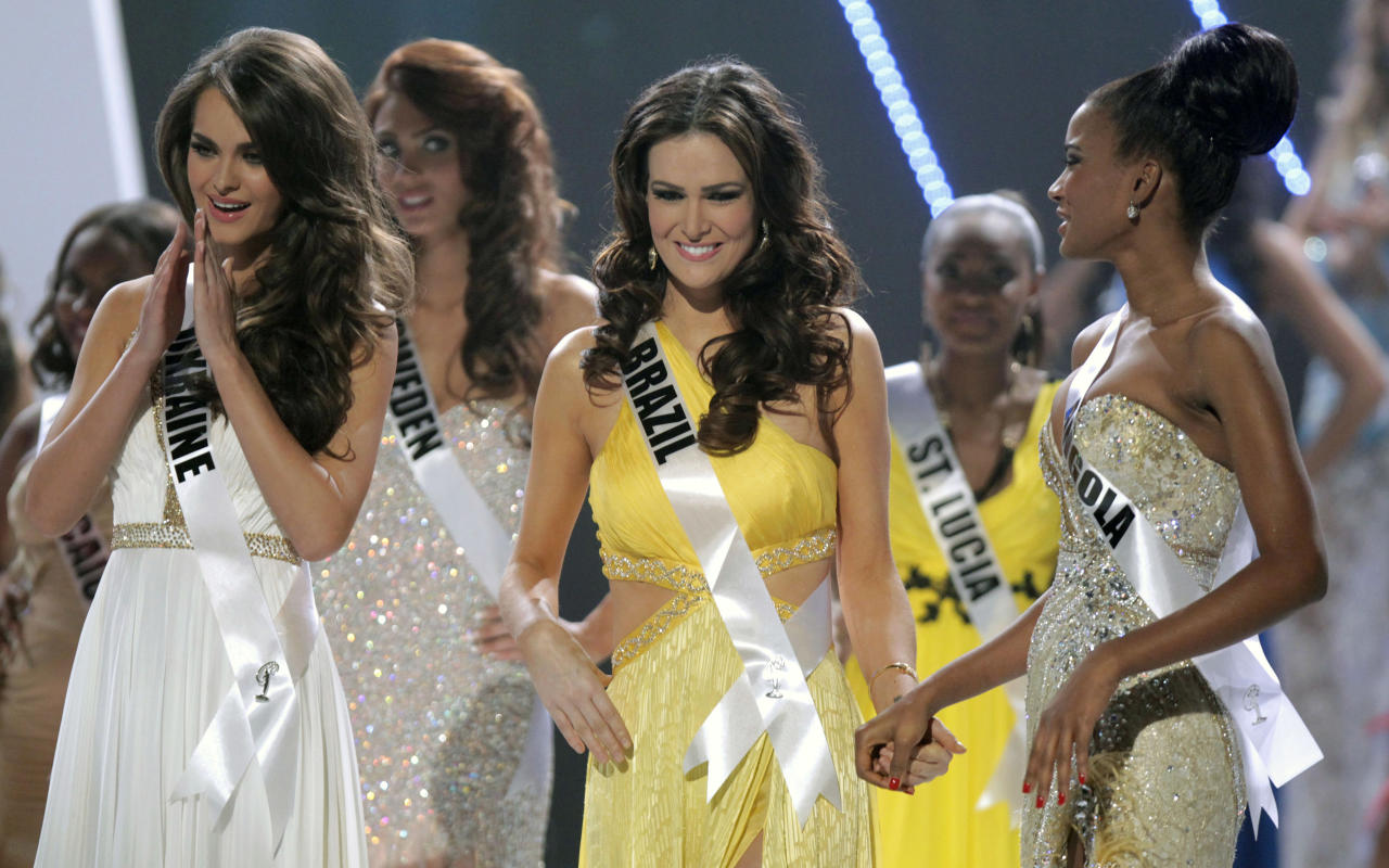 The top three finalists at the Miss Universe pageant, Miss Ukraine Olesia Stefanko, left, Miss Brazil Priscila Machado, center, and Miss Angola Leila Lopes react after Miss Brazil Priscila Machado was named second runner up during the pageant in Sao Paulo, Brazil, Monday, Sept. 12, 2011. Miss Ukraine Olesia Stefanko was first runner up and Miss Angola Leila Lopes won the crown. (AP Photo/Andre Penner)