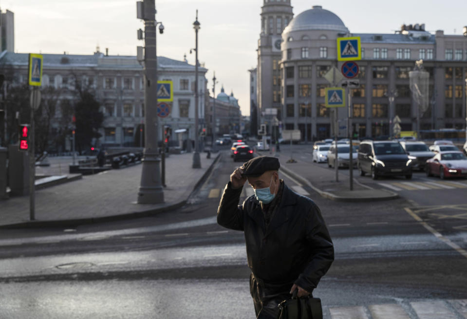 A man wearing a face mask to protect against coronavirus walks along a street in Moscow, Russia, Wednesday, Dec. 2, 2020. Russia has registered a record number of coronavirus deaths for a second straight day. (AP Photo/Pavel Golovkin)