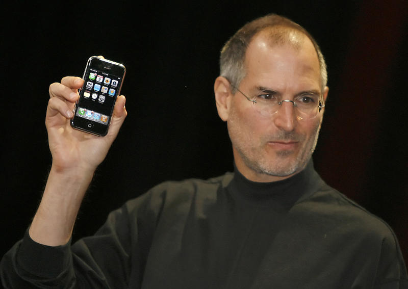 "Apple chief executive Steve Jobs unveils a new mobile phone that can also be used as a digital music player and a camera, a long-anticipated device dubbed an ""iPhone."" at the Macworld Conference 09 January 2007 in San Francisco, California. The ""iPhone"" will be ultra-slim -- less than half-an-inch (1,3 centimeters) thick -- boasting a phone, Internet capability and an MP3 player as well as featuring a two megapixel digital camera, Jobs said. (Photo credit should read TONY AVELAR/AFP/Getty Images)"
