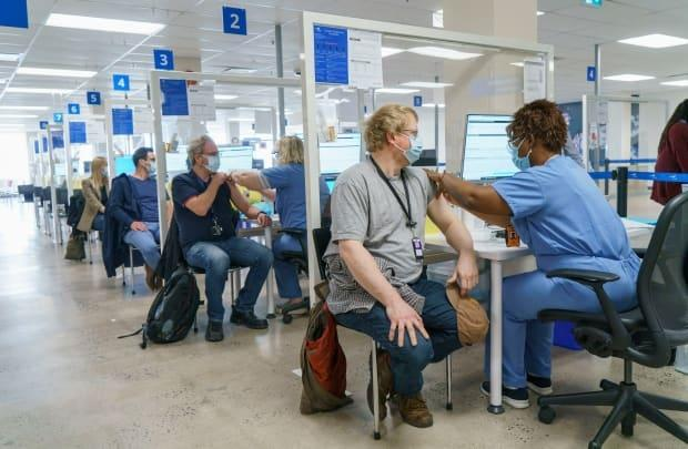 Workers are vaccinated at a clinic in Montreal. The exact percentage of the population that needs to be fully vaccinated or recovered from COVID-19 in order to reach herd immunity is uncertain and can change. Recent estimates put the threshold as high as 80 or close to 90 per cent.