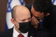 Israeli Prime Minister Naftali Bennett is spoken to as he attends a cabinet meeting at the prime minister's office in Jerusalem, Sunday, Aug. 1, 2021. (Abir Sultan/Pool Photo via AP)