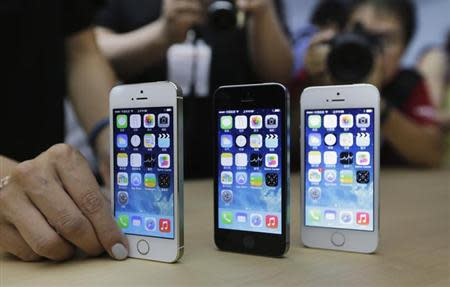 A staff member sets up the new iPhone 5Ss for a display picture at Apple Inc's announcement event in Beijing, September 11, 2013.