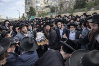 Ultra-Orthodox Jews carry the body of prominent rabbi Meshulam Soloveitchik during his funeral in Jerusalem, Sunday, Jan. 31, 2021. The mass ceremony took place despite the country's health regulations banning large public gatherings, during a nationwide lockdown to curb the spread of the virus. (AP Photo/Ariel Schalit)
