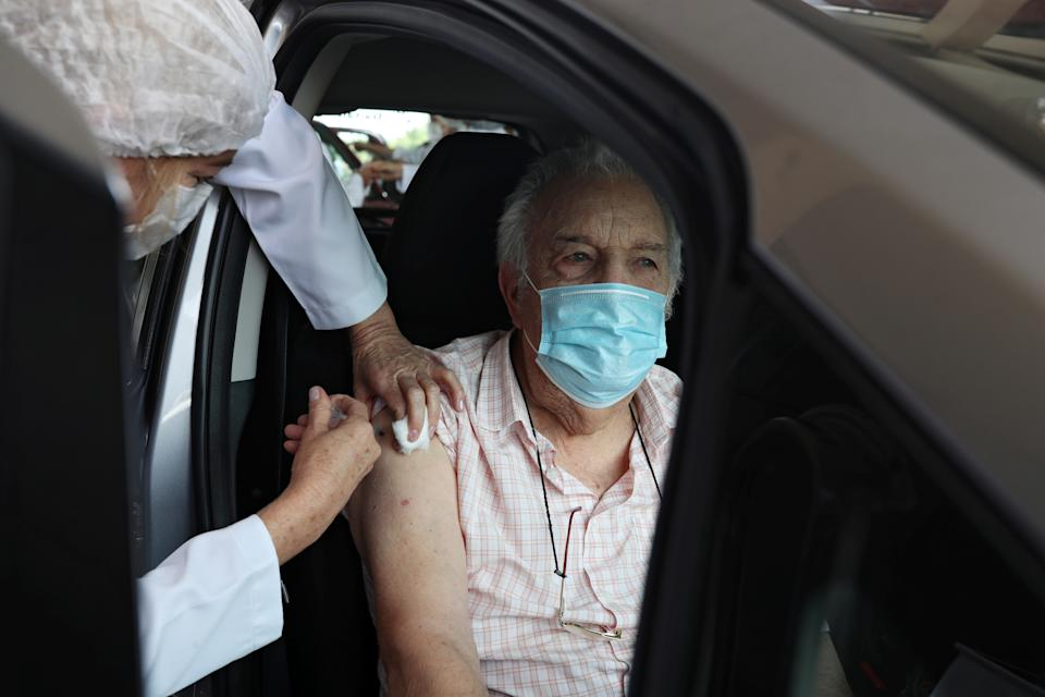 Jose Landi, 90, receives a dose of the coronavirus disease (COVID-19) vaccine at a drive-thru vaccination station for people aged 90 years or older at Pacaembu stadium in Sao Paulo, Brazil February 8, 2021. REUTERS/Amanda Perobelli