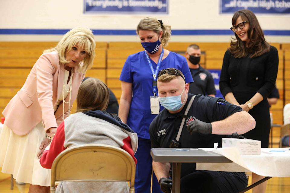 Jennifer Garner (R) looks on as first lady Jill Biden speaks with a child getting vaccinated at Capital High School in Charleston, West Virginia on May 13, 2021.