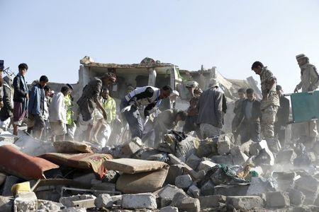 Civil defence workers and people search for survivors under the rubble of houses destroyed by an air strike near Sanaa Airport March 26, 2015. REUTERS/Khaled Abdullah