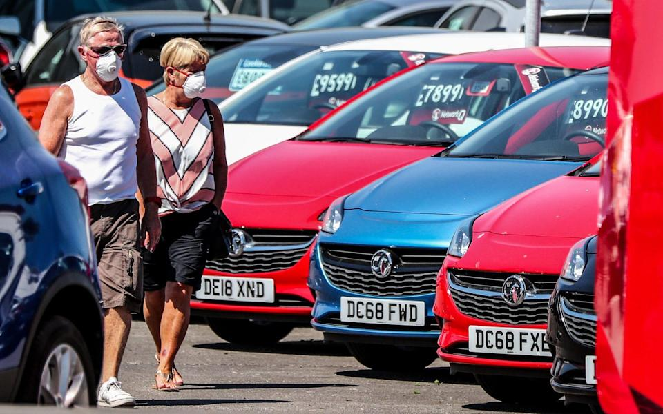 A couple walk past cars on the forecourt of Vauxhall Lookers in Speke, Liverpool - Peter Byrne