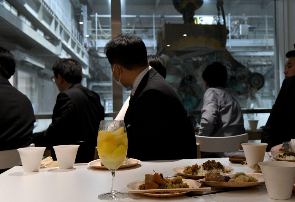 "<p>This photo shows customers watching an enormous crane pick up rubbish for incineration at a combustible waste pit while having a drink and snack at the ""Gomi Pit"" bar in Tokyo. The pop-up bar – called Gomi (trash) Pit – is the initiative of local officials who are trying to promote their state-of-the-art facility and prod local residents to think about the waste they produce. (Photo from Toshifumi Kitamura/AFP/Getty Images) </p>"