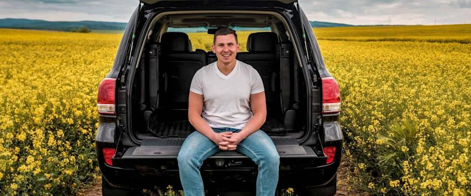 smiled young man sitting in the trunk of a car in yellow rape field