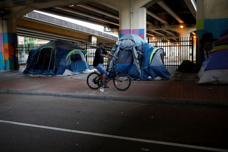 A homeless man on a bicycle rides past tents under an expressway ahead of Hurricane Ida, in New Orleans