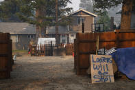 A warning sign is placed outside an evacuated home as fire crews continue to battle the Caldor Fire in Meyers, Calif., Friday, Sept. 3, 2021. Fire crews took advantage of decreasing winds to battle a California wildfire near popular Lake Tahoe and were even able to allow some people back to their homes but dry weather and a weekend warming trend meant the battle was far from over. (AP Photo/Jae C. Hong)
