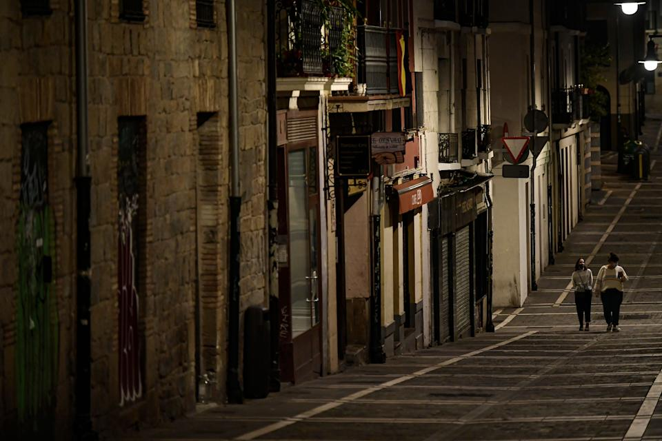 Residents wearing face masks as they walk along an empty Javier street, in Pamplona, northern Spain (AP Photo/Alvaro Barrientos) (Photo: ASSOCIATED PRESS)