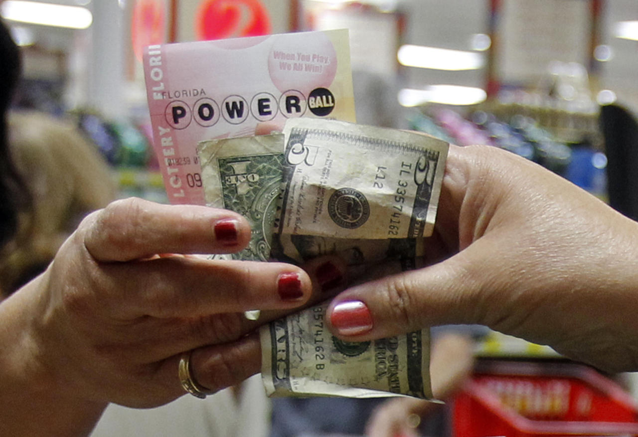 A customer buys three Powerball tickets at a local supermarket in Hialeah, Fla.,Tuesday, Nov. 27, 2012. There has been no Powerball winner since Oct. 6, and the jackpot already has reached a record level for the game. Already over $500 million, it is the second-highest jackpot in lottery history, behind only the $656 million Mega Millions prize in March. (AP Photo/Alan Diaz)